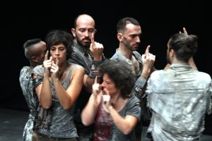 A group of 5 Portuguese actors each with the hands raised and fingers pointing up, facing in different directions