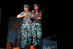 2 Croatian women playing one character, dressed in identical camouflage and beret.